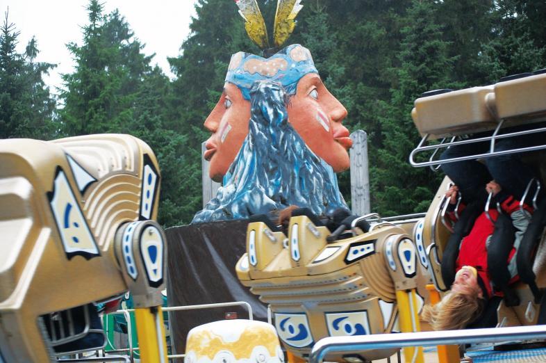 Foto einer doppelgesichtigen Skulptur eines Kopfes als Dekoration eines Fahrgeschäfts.