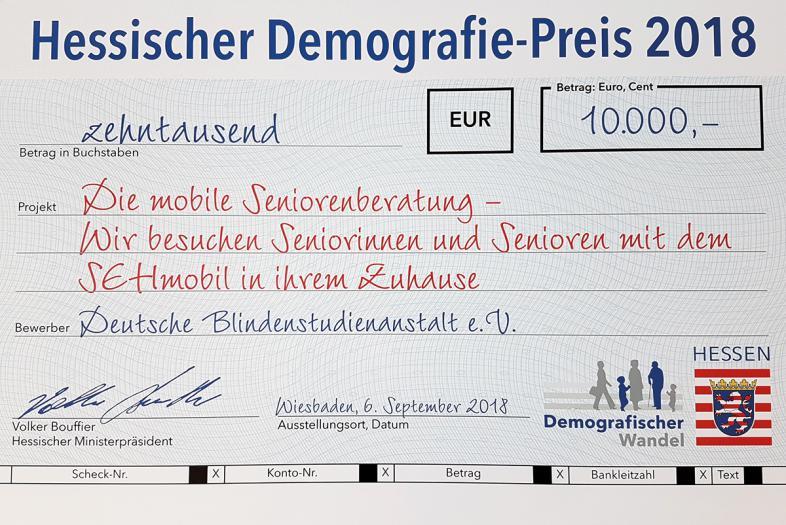 Der symbolische Scheck über den Preisgewinn von 10.000 €