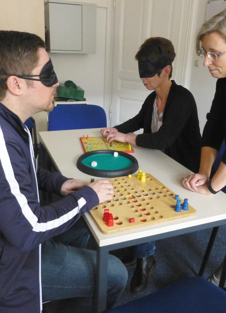 Unter Anleitung machen 2 Teilnehmende Erfahrungen mit dem Spiel Mensch-ärgere-Dich-nicht
