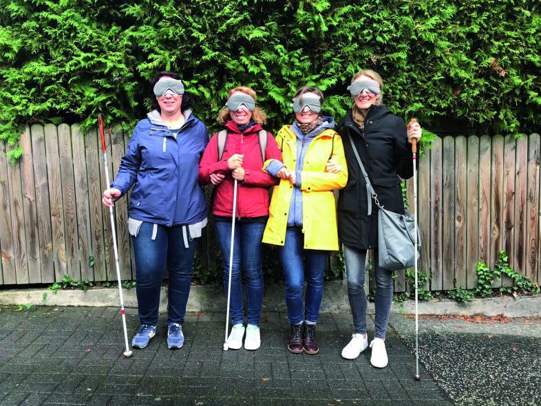Vier Erwachsene sind mit Augenbinden und Langstöcken ausgestattet.