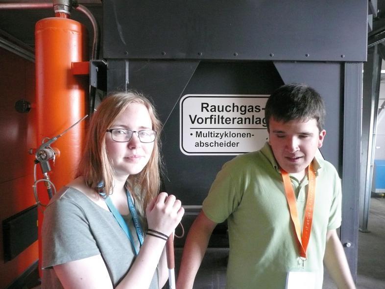 Die Schüler Anna und Max vor einem Rauchgasfilter
