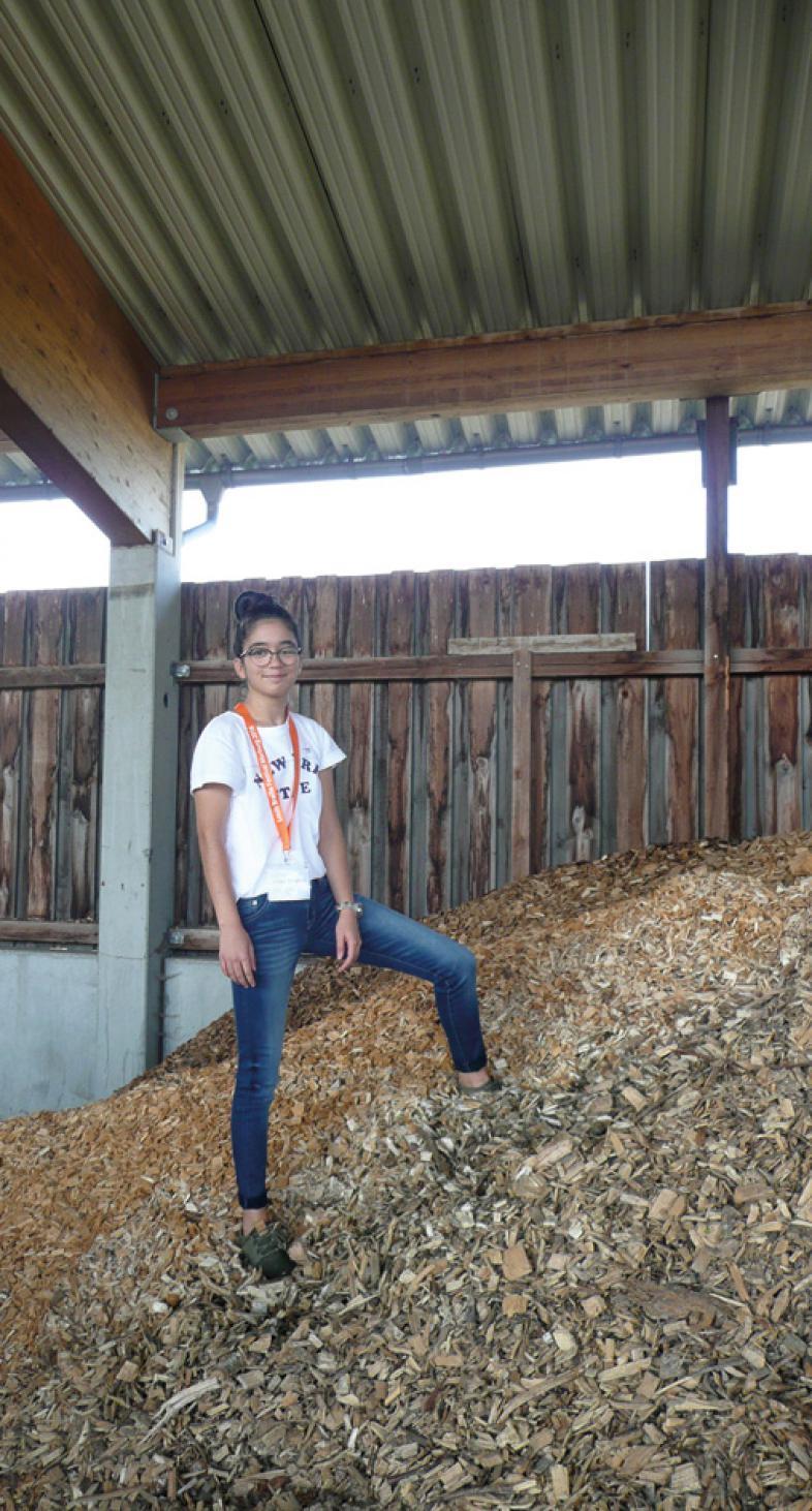 Schülerin Sezen steht auf einem großen Holzschnitzelhaufen