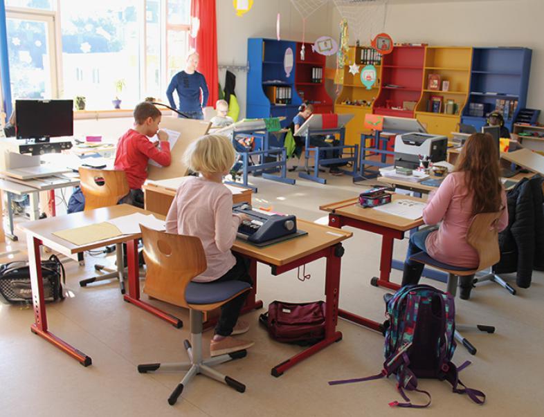 Das Foto zeigt die Schülerinnen und Schüler in ihrem fröhlich-bunt gestalteten Klassenraum