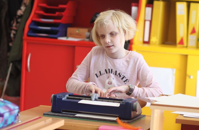 Eine Schülerin an ihrem blindengerecht gestalteten Platz