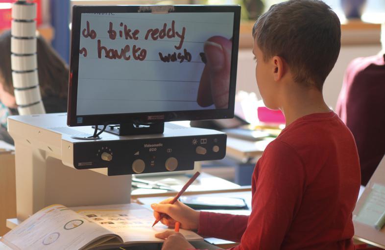 Ein Schüler an seinem sehbehindertengerecht gestalteten Platz