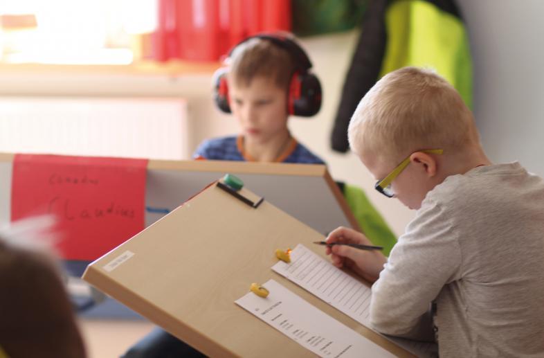 Zwei Fünftklässler arbeiten im Unterricht, der eine mit, der andere ohne Schallschutzkopfhörer