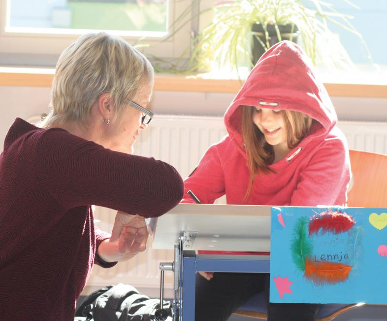 Die Klassenlehrerin erläutert einer Schülerin eine Aufgabe.
