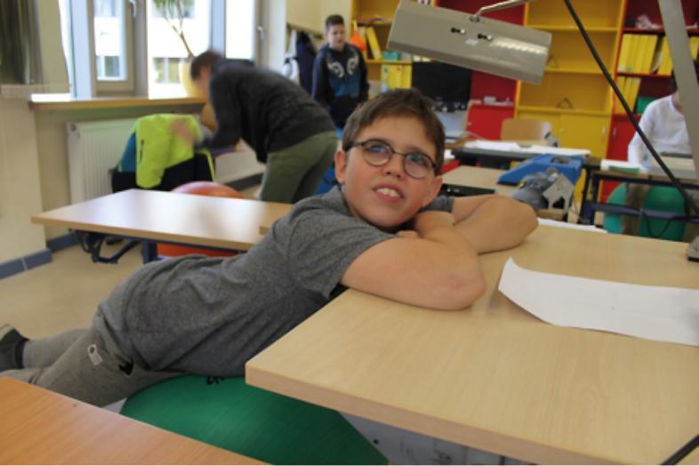 Ein Schüler lehnt sich bequem über seinen Tisch