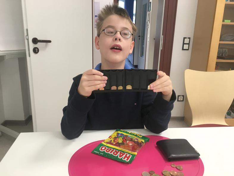 Ein Junge zeigt die Münzen, mit denen er eine Tüte Gummibärchen kaufen würde