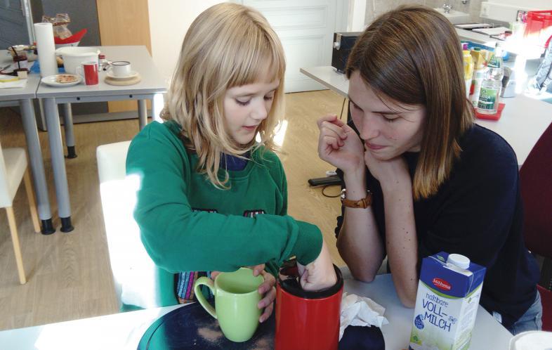 Getränke einschenken: Ein Mädchen übt mit einer Trainerin