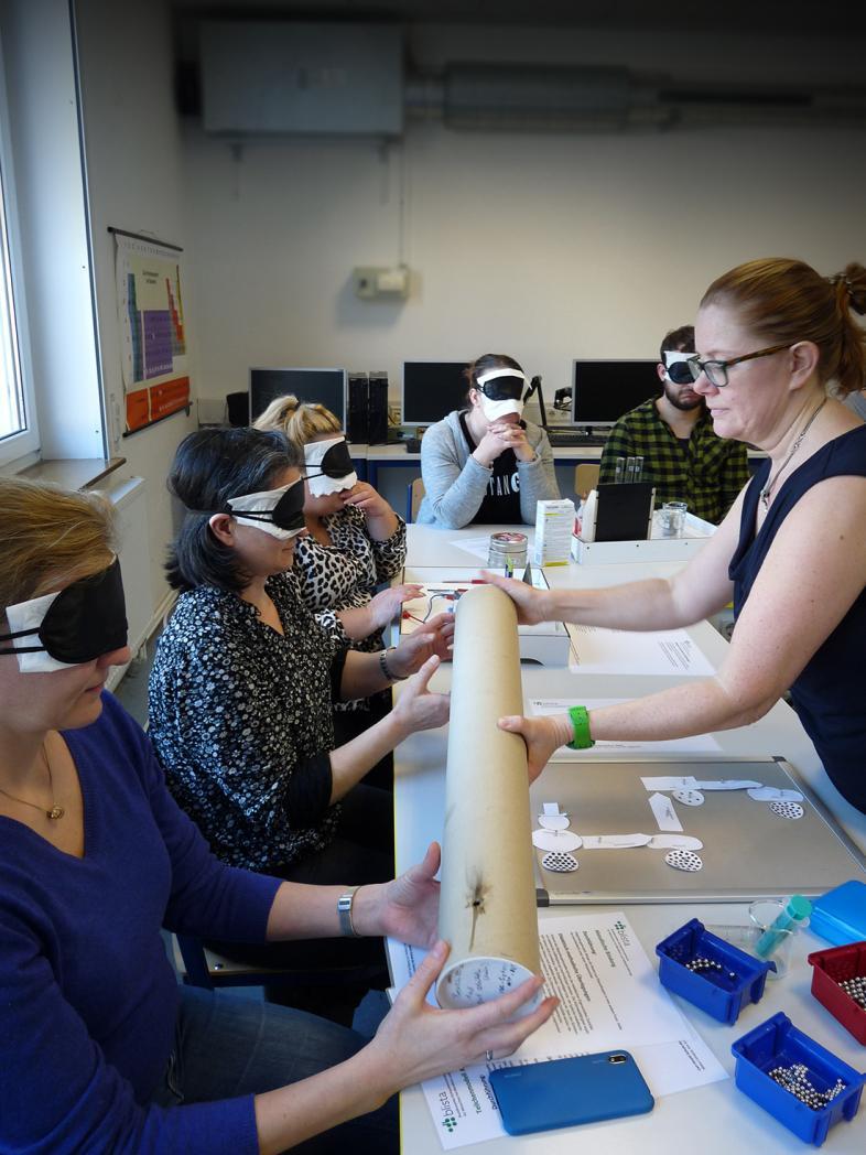 Selbsterfahrung unter der Augenbinde: Auf dem Foto sitzen 5 der Teilnehmenden an einem langen Tisch, auf dem sich diverse taktile Materialien befinden.