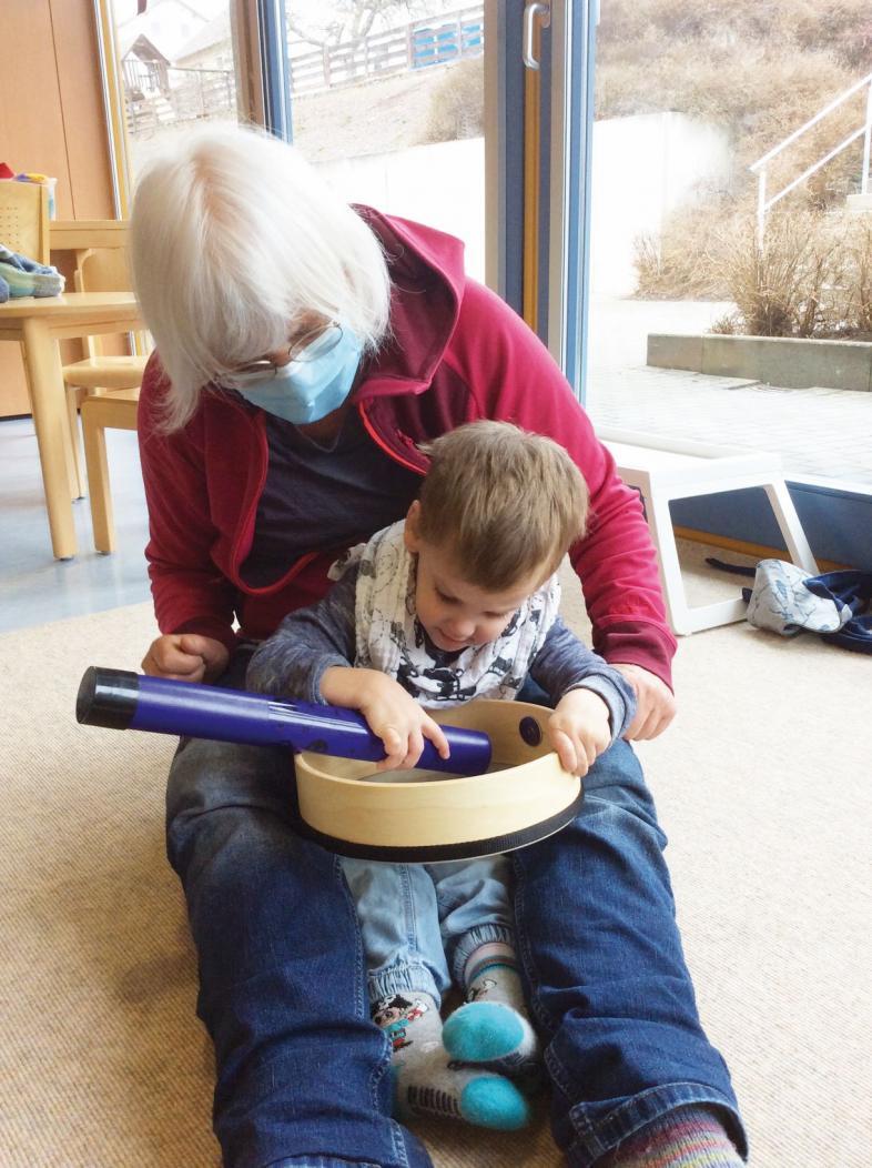 Ein Kleinkind untersucht Frühfördermaterial mit der Frühförderin
