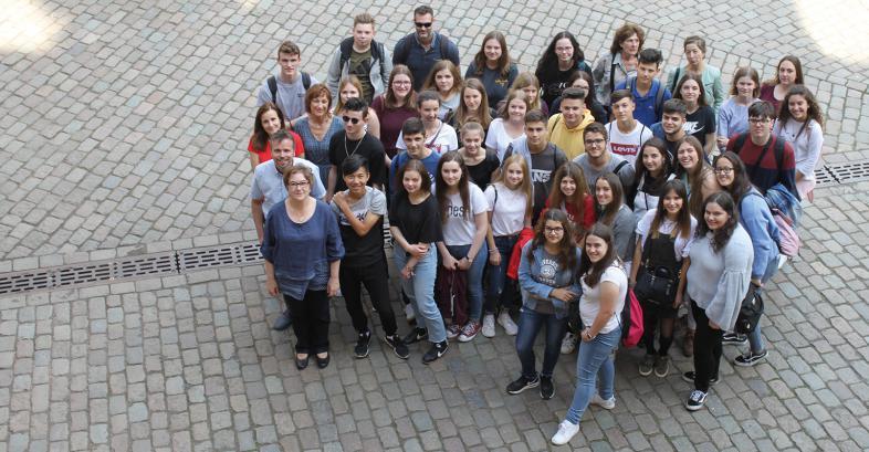 Eine Schülergruppe auf dem Marburger Rathausplatz - von oben, aus dem Rathaus, fotografiert.