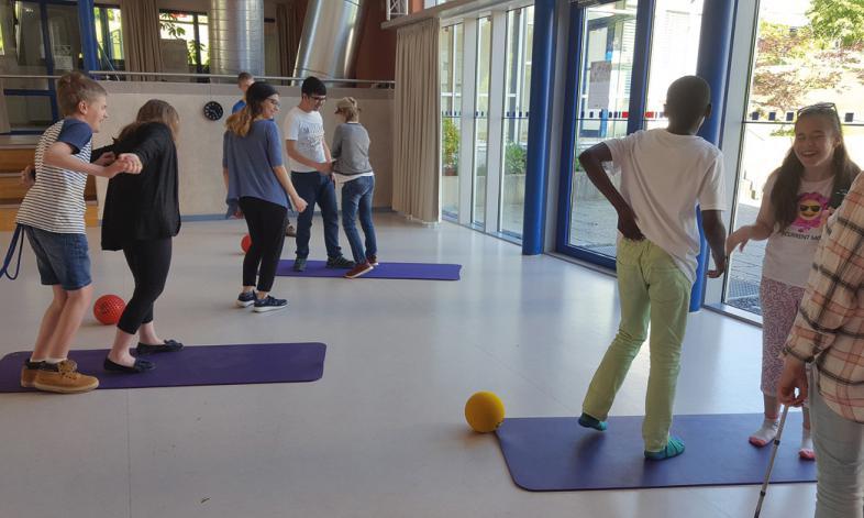 In der Aula sind Bodenmatten und Bälle ausgeliegt, den Schülern macht das Bewegen Spaß.