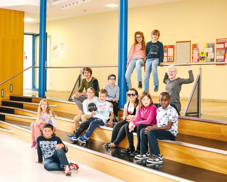 11 Schülerinnen und Schüler sitzen auf den Stufen der blista-Aula, daneben Klassenlehrer Florian Ott