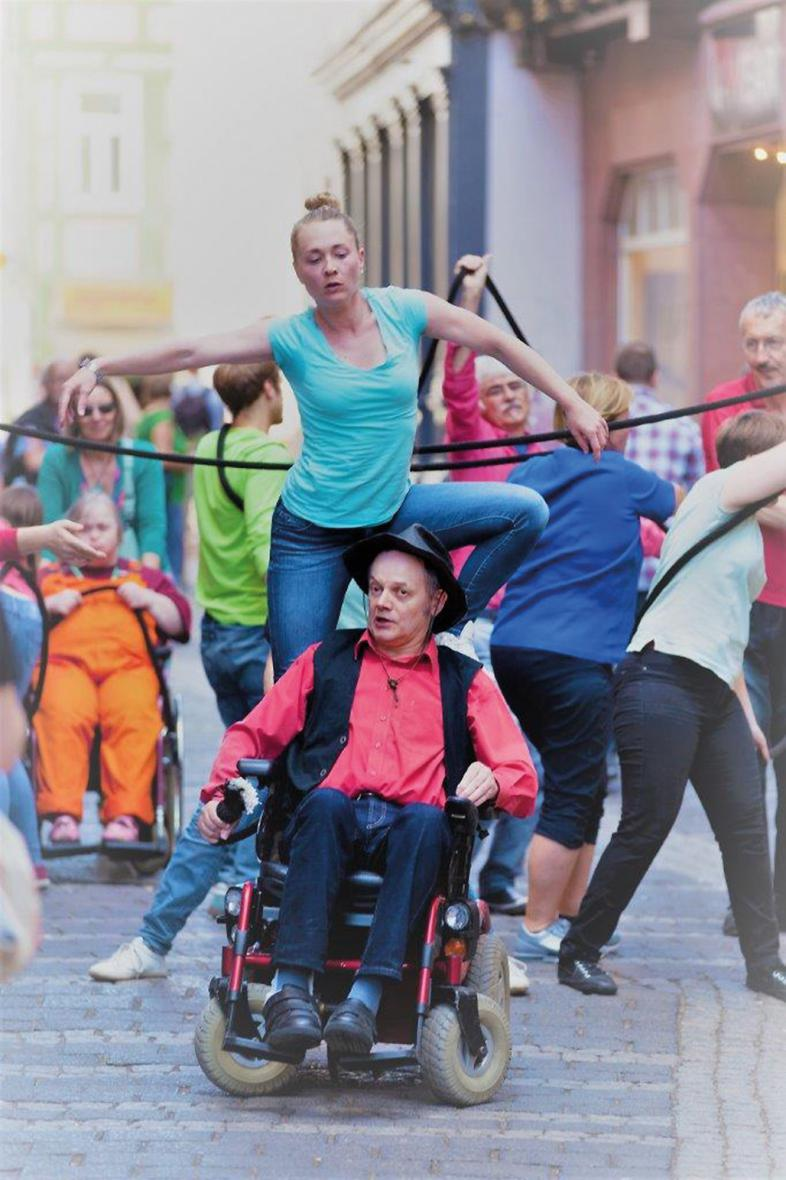 8 bunt gekleidete Hürdenläufer mit einem dicken Seil