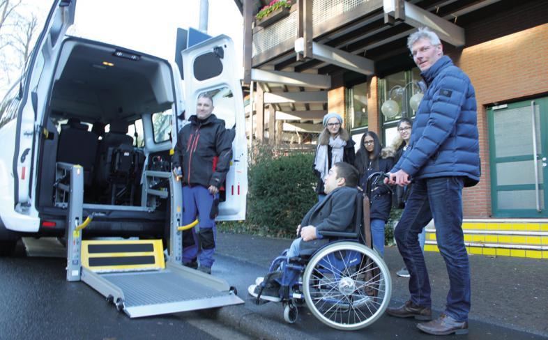 Internatsleiter Maarten Kubeja schiebt einen Schüler in den Rollibus