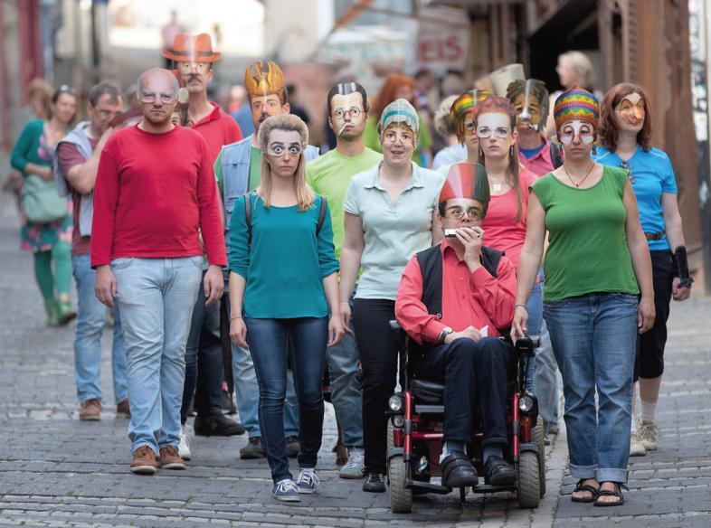 Gruppenbild mit bunten T-Shirts und Masken