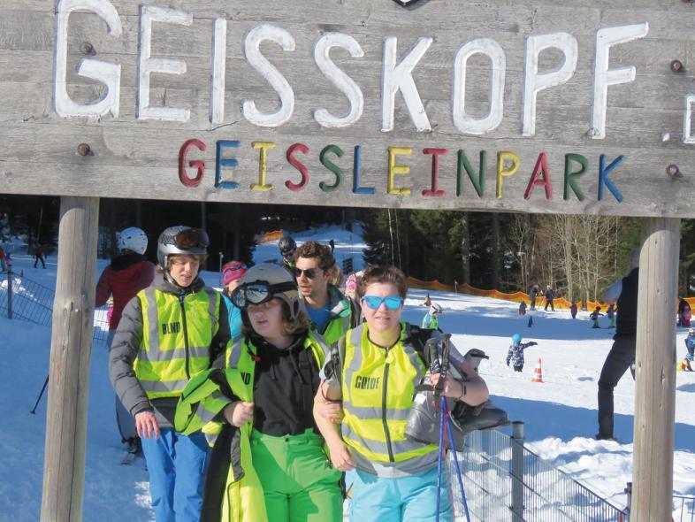"""Vier Schüler wandern durch das große Holzschild mit der Aufschrift """"Geisskopf"""""""