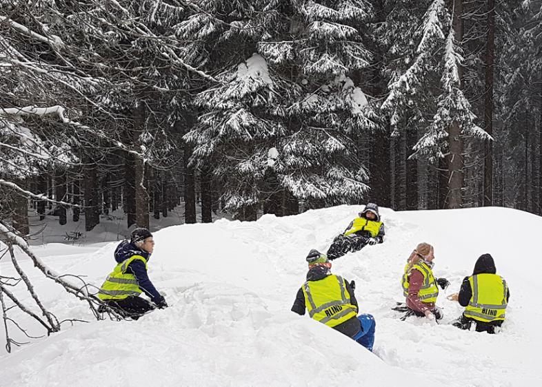 5 Personen hocken, sitzen und liegen auf einer Schneefläche, die von hohen Tannen umgeben ist.