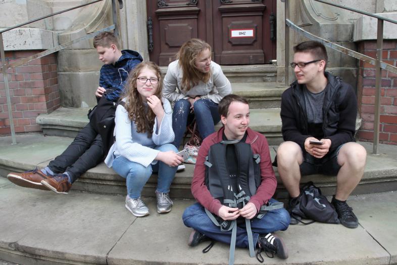 5 unternehmungslustige Schüler sitzen auf Treppenstufen