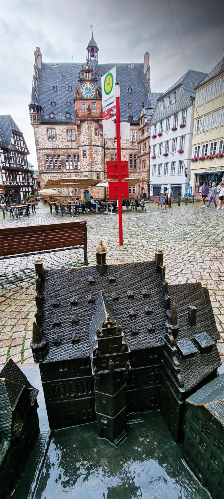 Foto quer über den Marburger Marktplatz mit der leuchtend roten Bushaltestelle im vordergrund und der Frontansicht des Rathauses im Hintergrund