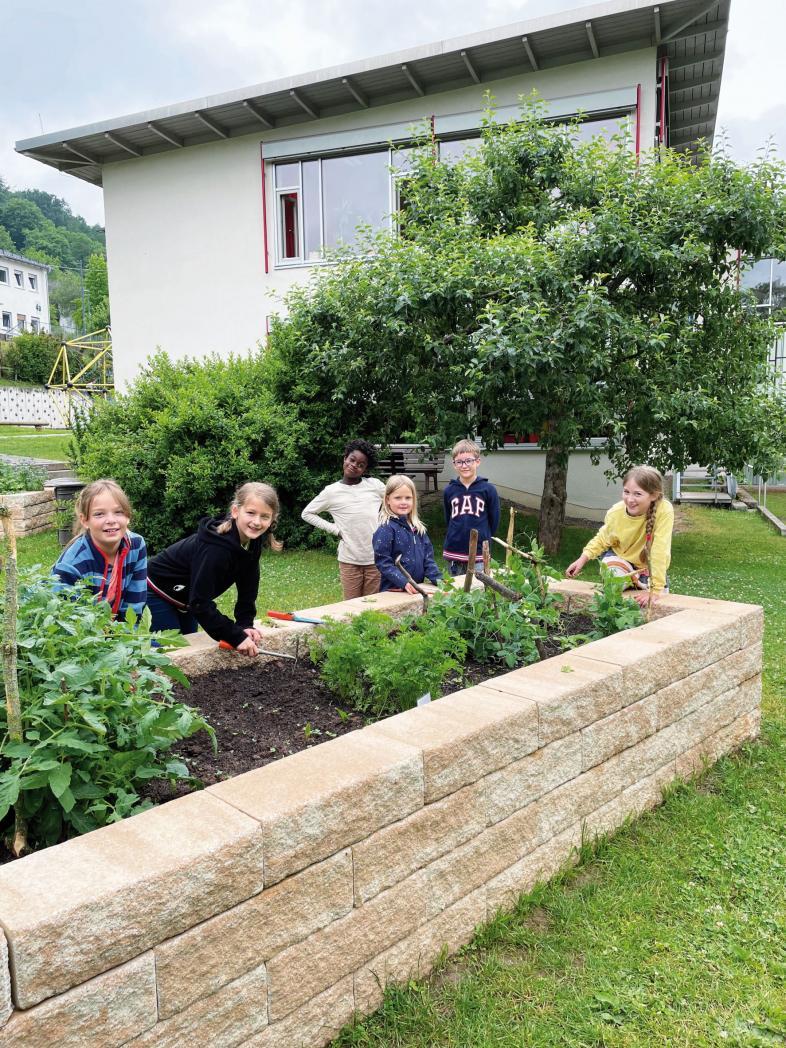 Das Foto zeigt sechs Montessori-Schülerinnen und Schüler am Hochbeet.