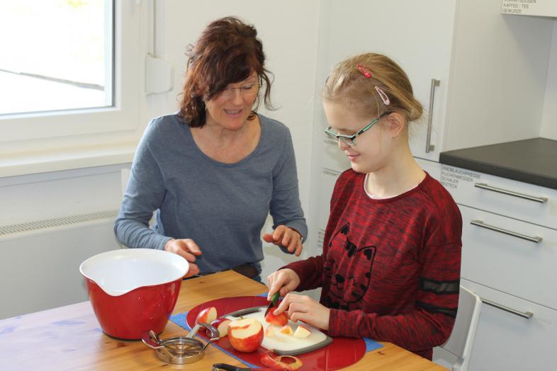 Eine Rehalehrerin zeigt einer blinden Schülerin das Aufschneiden von Äpfeln