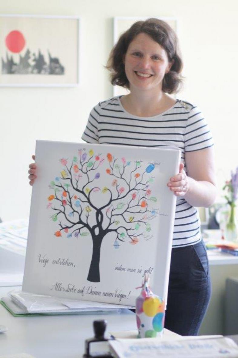 Frau Quatram mit ihrem Abschiedsbild, einem Unterschriftenbaum