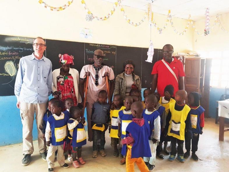 Das Foto zeigt 16 Kinder in Schuluniform und fünf Erwachsene im Klassenraum