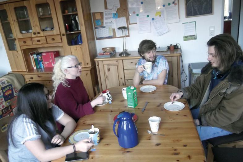 4 junge Leute sitzen bei (den Resten von) Kaffee und Kuchen um einen Tisch