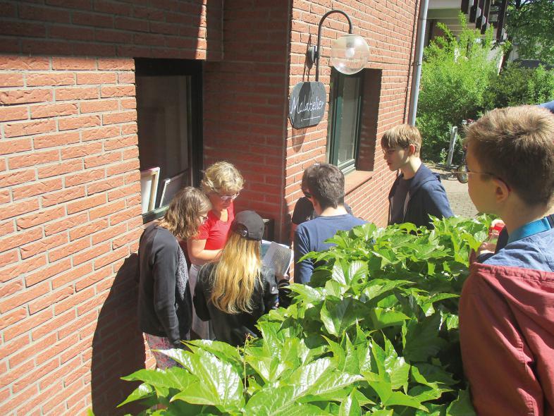 Beim Malatelier geht es los, Frau Dirmeier liest, den Teilnehmenden vor, was auf der Anweisung steht.