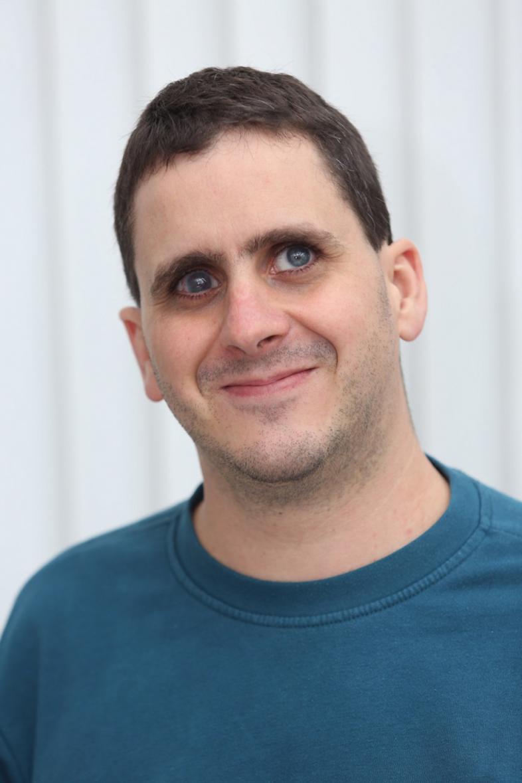 Jens Flach trägt sein dunkles Haar kurz geschnitten, er lächelt zu den Betrachtenden hin (Portraitfoto)