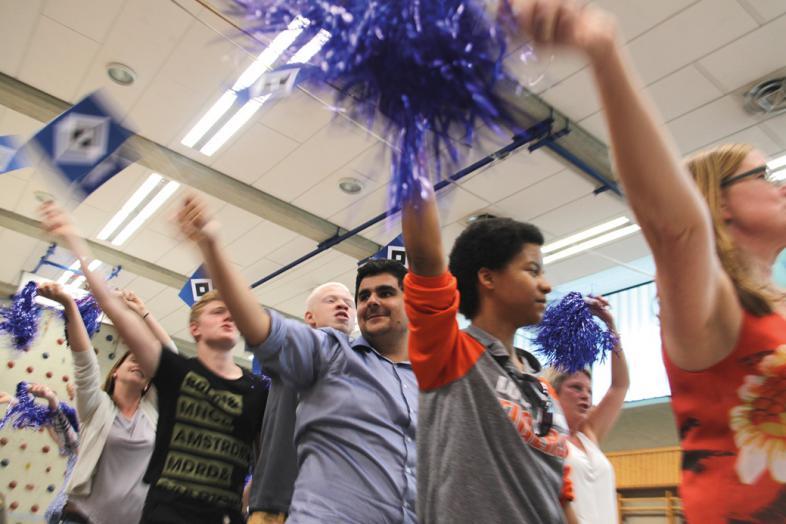 Schüler schwingen blaue Fahnen und glitzernde Puschel