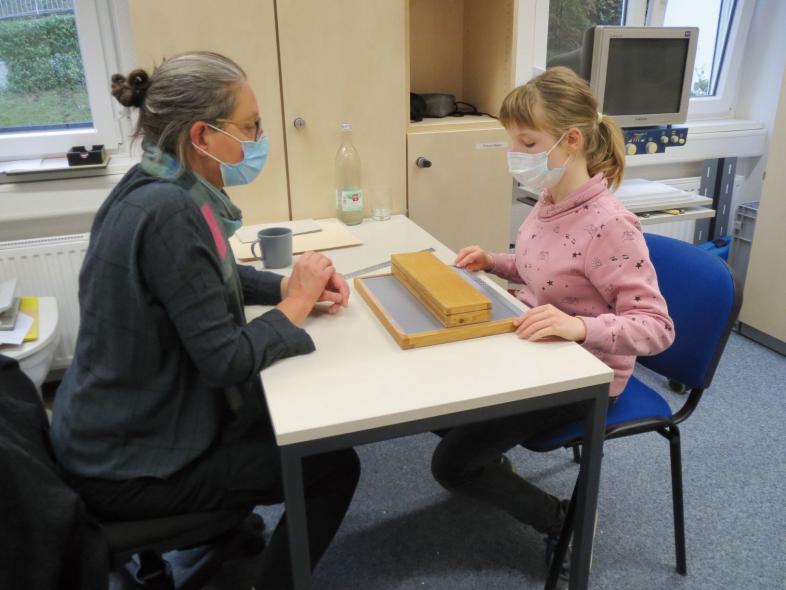 Katja Jung  und Alex arbeiten am Tisch.