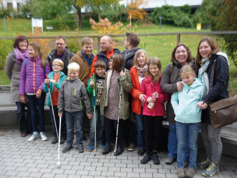 Das Foto zeigt die große vergnügte Gruppe der Kinder, Eltern und Fachkräfte