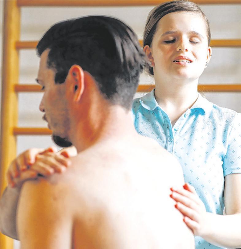 Lea Respondek  im TherapiecentrumVoxtrup, ihre Hände liegen auf Rücken und Schulter vor einem Klienten