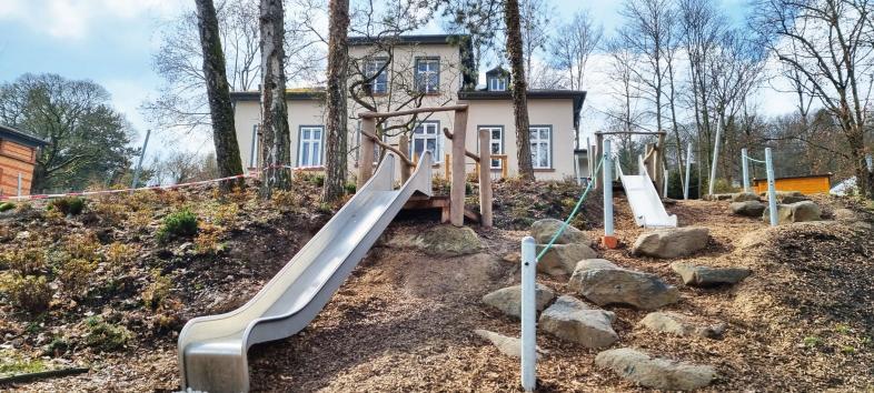 Foto des Kinderhauses und des Spielgeländes mit Rutschen und Spiellandschaft
