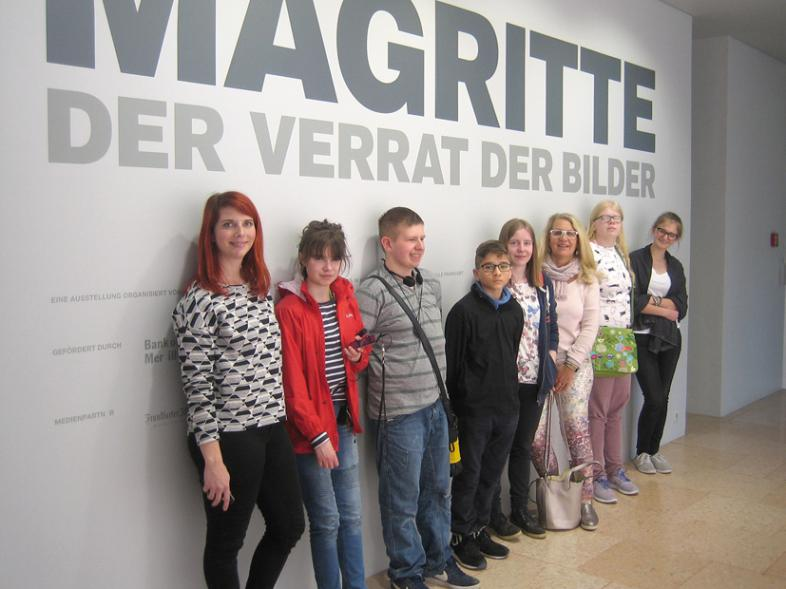 Ein Gruppenbild vor dem Banner in der Eingangshalle der Ausstellungsräume