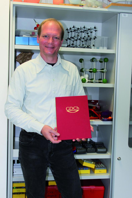 Tobial Mahnke posiert mit seiner Urkunde vor einem Regal mit Chemiemodellen.