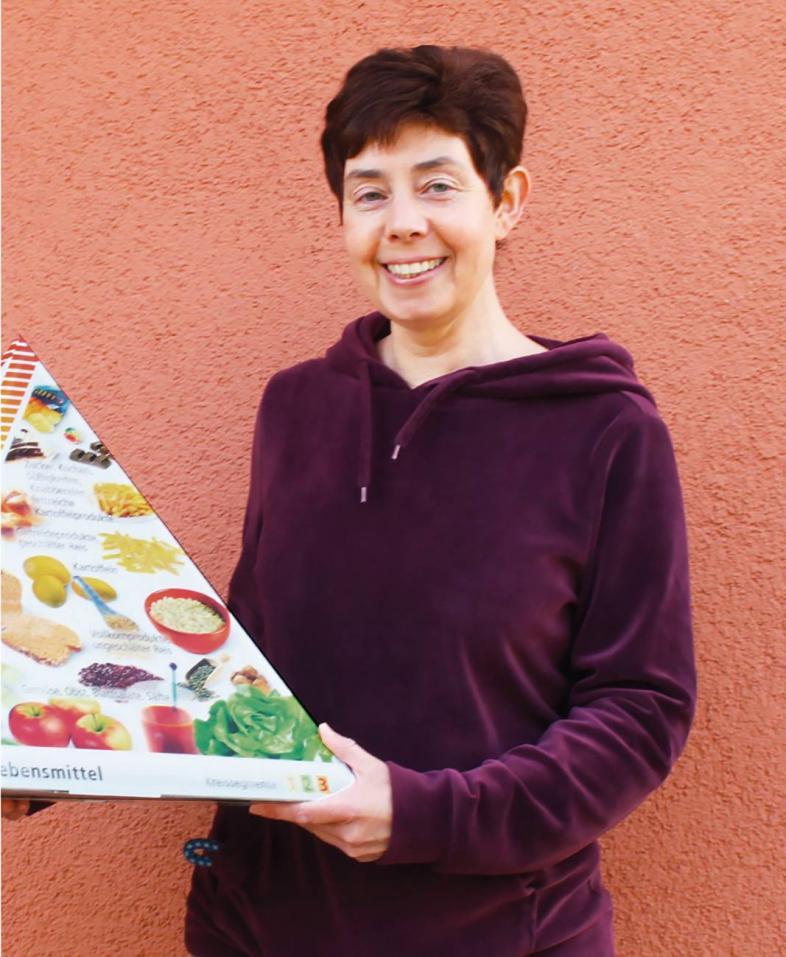 Maike Kroll zeigt eine Ernährungspyramide aus Pappe