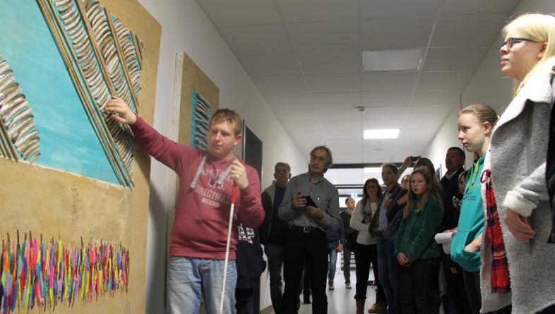 Ein Schüler zeigt erklärend auf eine taktile Installation