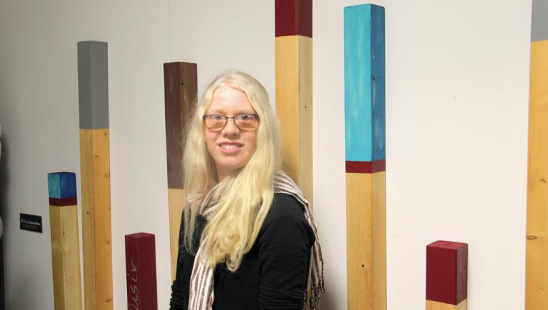Eine Schülerin mit langen blinden Haaren, im Hintergrund das taktile Bild
