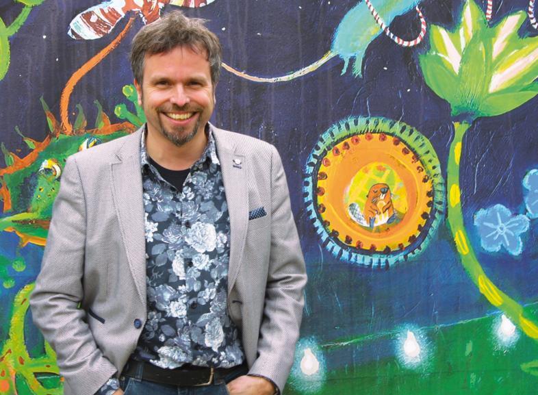 Porträt von Markus Biber vor einer bunt bemalten Wand