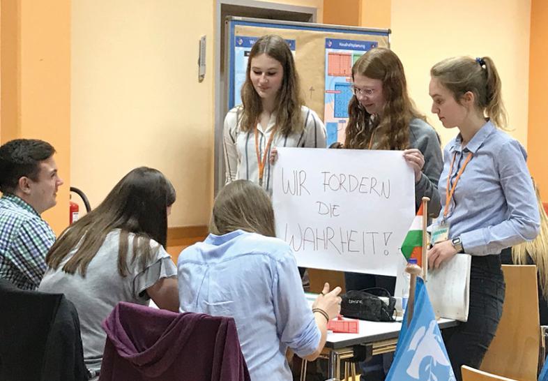 """6 junge Leute arbeiten in einer Gruppe zusammen. 3 halten als Delegation ein Plakat mit der Aufschrift """"Wir fordern die Wahrheit""""."""