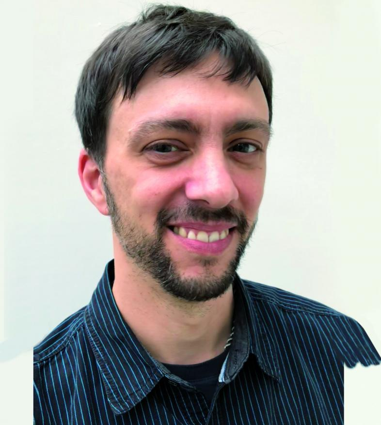 Portraitfoto von Kevin Reuter. Er hat kurze dunkelbraune Haare, eine dunklen 7-Tage-Bart und lächelt in die Kamera.