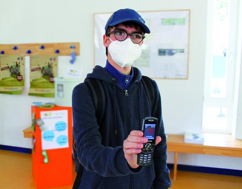 Adrian als Retrotechnikfan präsentiert ein altes Mobiltelefon