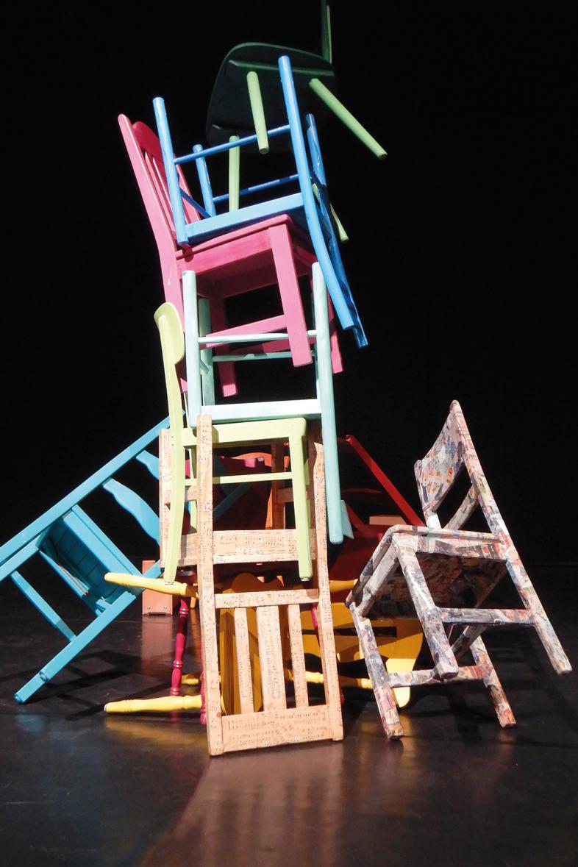 Das Foto zeigt bunte hoch gestapelte Stühle