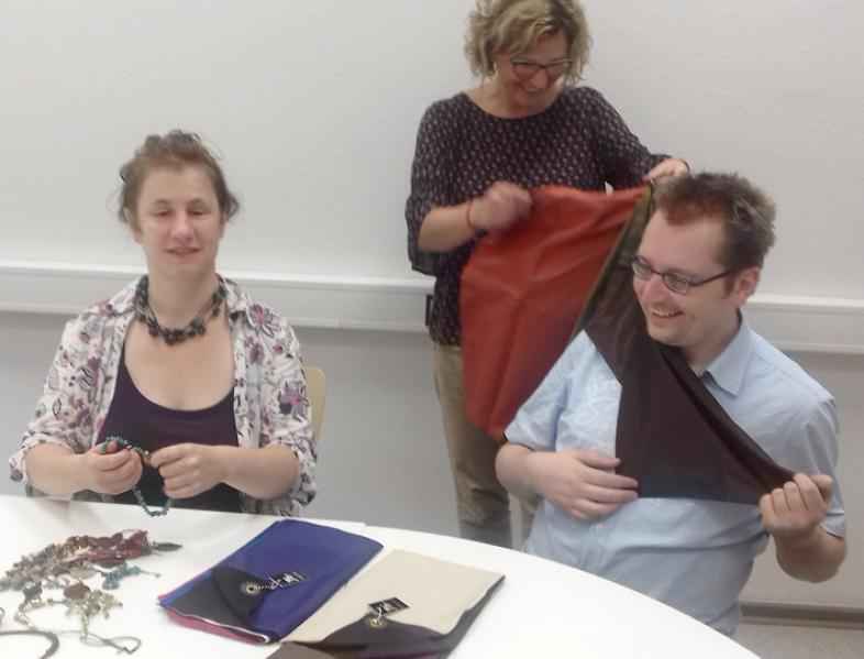Die Dozentin erarbeitet mit einem Teilnehmenden vergnügt passende Farbmuster, während eine Dritte unterschiedliche Halsketten ausprobiert.