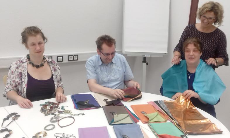 3 Teilnehmende mit Dozentin, auf dem Tisch vor ihnen sind Farbmuster verteilt